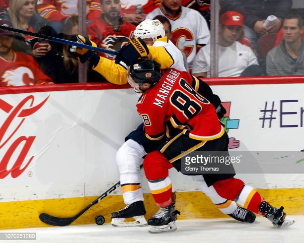 Nashville Predators Defenceman Ryan Ellis and Calgary Flames Forward Andrew Mangiapane battle for the puck during an NHL game on December 8, 2018 at...