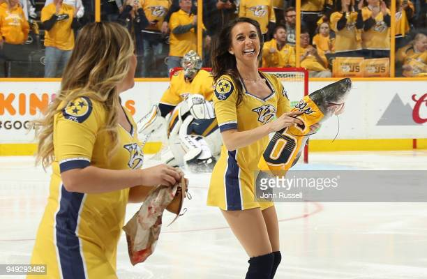 Nashville Predators Energy Team skaters remove a catfish from the ice prior to Game Five of the Western Conference First Round against the Colorado...