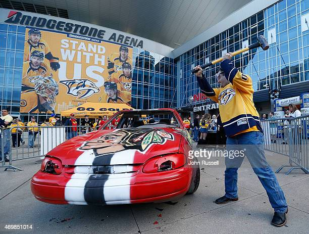 Nashville Predators fan Adam Kirk takes a swing at the Blackhawks car on the plaza before Game One of the Western Conference Quarterfinals against...