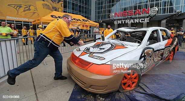 Nashville Predators fan takes swing at an Anaheim Ducks themed car prior to Game Three of the Western Conference First Round between the Nashville...