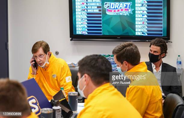 Nashville Predators GM David Poile answers a call prior to announcing his pick at as team captain Roman Josi looks on during Round One of the 2020...
