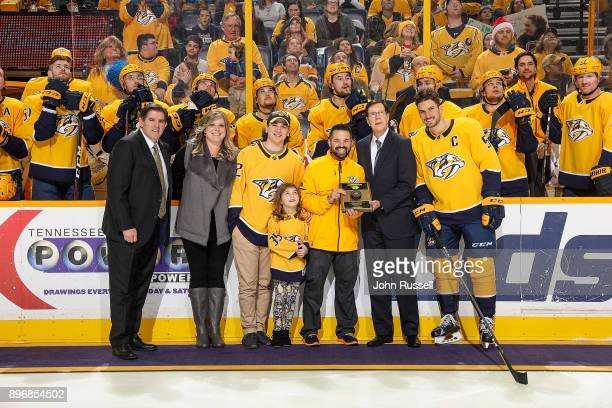 Nashville Predators GM David Poile, head coach Peter Laviolette and Roman Josi present a plaque to assistant equipment manager Jeff Camelio with his...