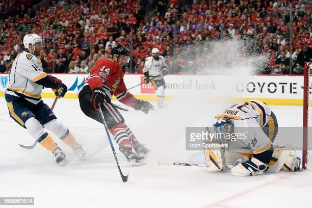 Nashville Predators goalie Pekka Rinne covers the puck from Chicago Blackhawks right wing Richard Panik as he stops and sprays ice over him in the...