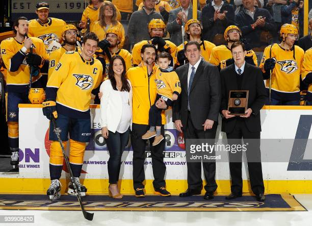 Nashville Predators head athletic trainer Andy Hosler is honored for his 1000th NHL game with his wife, Elizabeth and son Henry by GM David Poile,...
