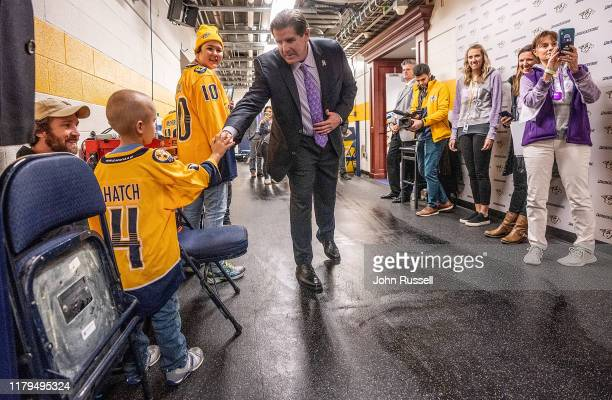 Nashville Predators head coach Peter Laviolette greets cancer patient Sam Hatch during the Hockey Fights Cancer game against the New York Rangers at...