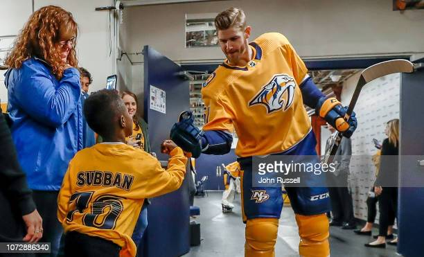 Nashville Predators left wing Austin Watson highfives a young fan prior to an NHL game against the Vancouver Canucks at Bridgestone Arena on December...