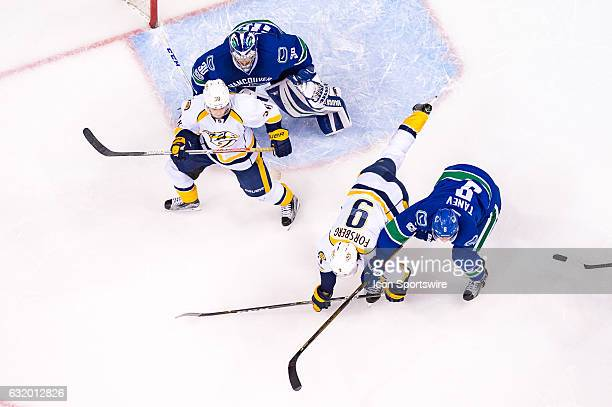 Nashville Predators Left Wing Filip Forsberg is checked to the ice by Vancouver Canucks Defenceman Chris Tanev as Nashville Predators Left Wing...
