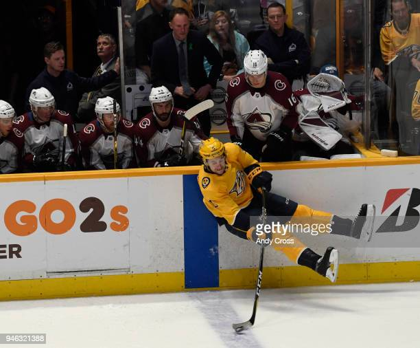 Nashville Predators left wing Filip Forsberg passes the puck as he fall down in the first period of play along the Colorado Avalanche bench during...