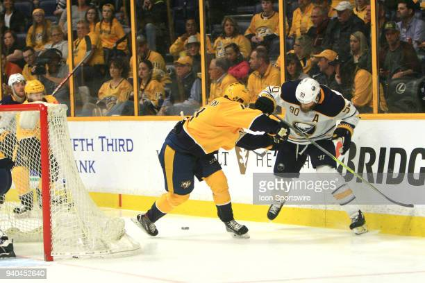 Nashville Predators right wing Eeli Tolvanen battles for the puck with Buffalo Sabres center Ryan O'Reilly during the NHL game between the Nashville...