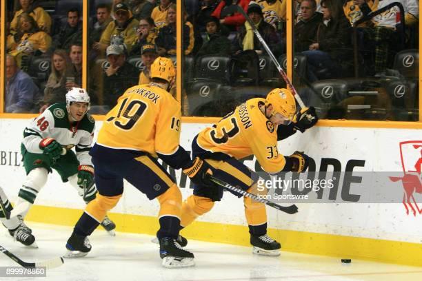 Nashville Predators winger Calle Jarnkrok shields Minnesota Wild defenseman Jared Spurgeon as Nashville Predators right wing Viktor Arvidsson pursues...