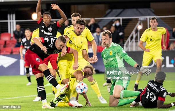 Nashville SC defender Taylor Washington and goalkeeper Joe Willis defend a shot by D.C. United midfielder Russell Canouse during an MLS match between...