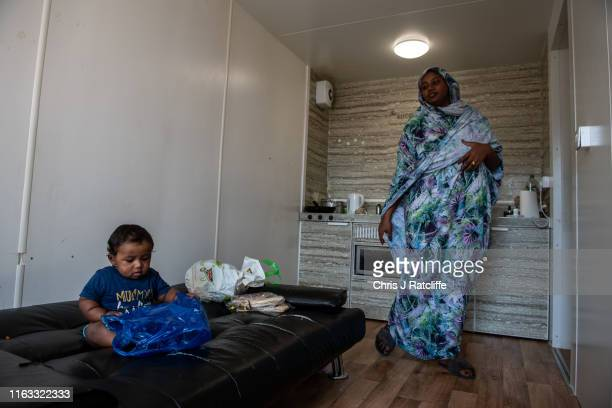 Nasibah Yagoub prepares lunch for her 7 month old son Youssef as her husband Abderrahim sleeps after working a night shift at a development of...