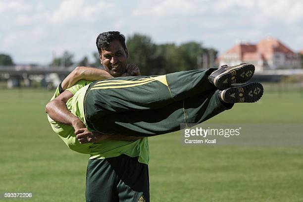 Nasir Ahmad from Fasalabad in Pakistan member of the Bautzen cricket team grapples with another team member during a break in a friendly match...