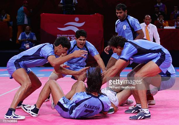 Nasir Ali of Pakistan is pounced upon by the Indian team during the Men's Kabaddi Gold Medal match between India and Pakistan at the 15th Asian Games...