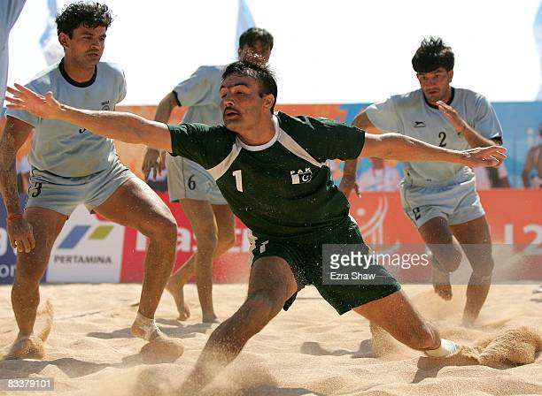 Nasir Ali of Pakistan tries to escape before being tackled by India during their beach kabaddi match on day five of the 2008 Asian Beach Games at...