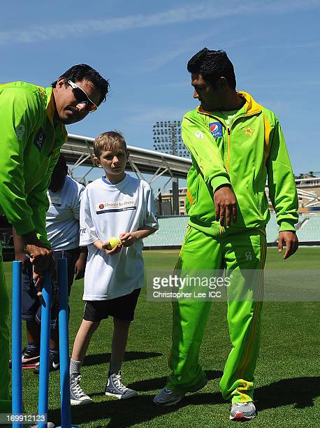 Nasir Jamshed and Asad Shafiq of Pakistan gives some tips to a young player as they play a game of cricket with young fans from Curwen Primary School...