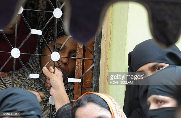 Nasreen Fatima wife of slain Indian soldier Lance Naik Mohammed Feroz Khan looks on during his funeral in Hyderabad on October 17 2013 Hundreds of...