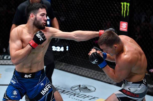 Nassourdine Imavov of Russia punches Ian Heinisch in their middleweight fight during the UFC Fight Night event at UFC APEX on July 24, 2021 in Las...
