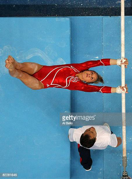 Nastia Liukin of the United States competes on the uneven bars while her coach spots her in the artistic gymnastics team event at the National Indoor...