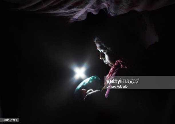 Nasuran Begham sits in the dark during an electricity cut holding her third child four days after giving birth in the a postnatal ward Assam India...