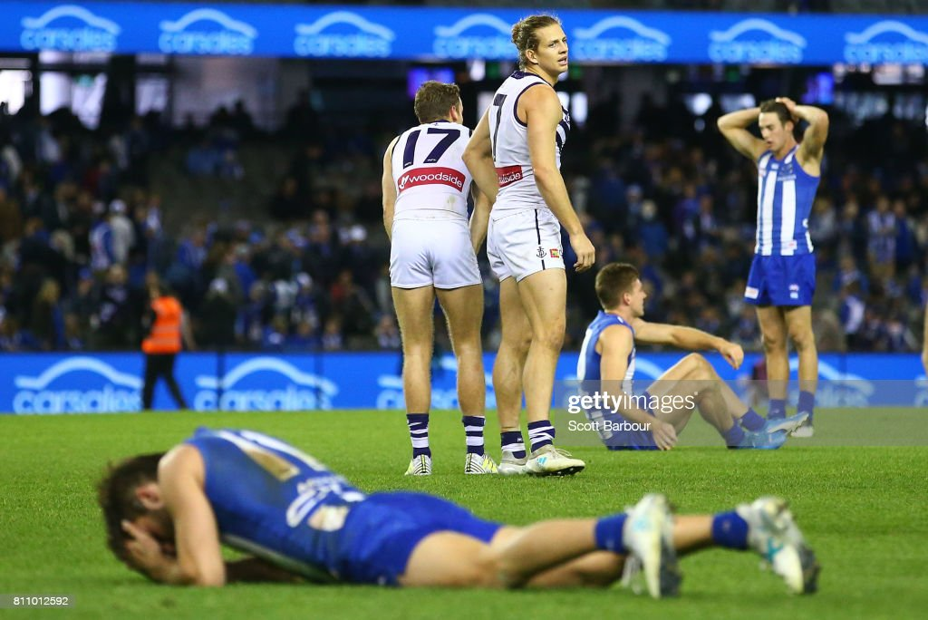 Nat Fyfe of the Dockers celebrates at the final siren as Kangaroos players look dejected during the round 16 AFL match between the North Melbourne Kangaroos and the Fremantle Dockers at Etihad Stadium on July 9, 2017 in Melbourne, Australia.