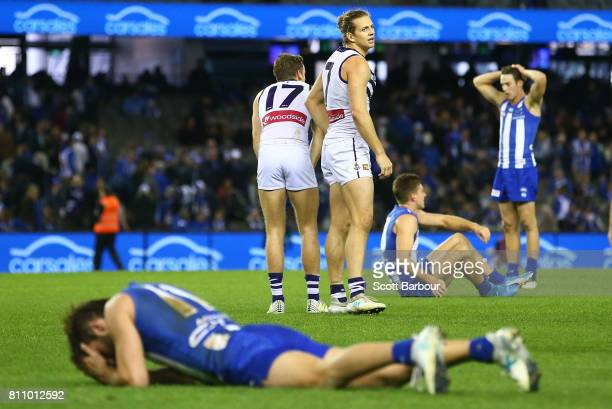 Nat Fyfe of the Dockers celebrates at the final siren as Kangaroos players look dejected during the round 16 AFL match between the North Melbourne...