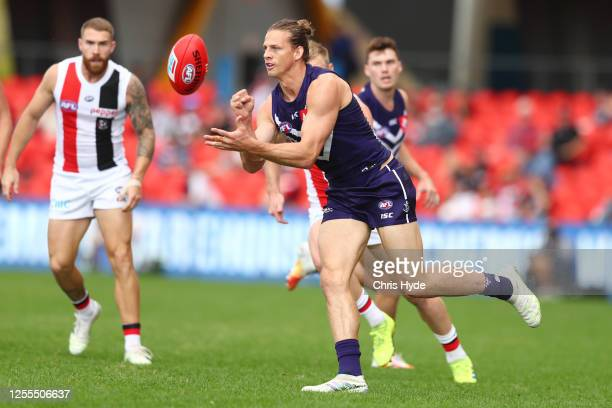 Nat Fyfe of the Dockers handballs during the round 6 AFL match between the Fremantle Dockers and the St Kilda Saints at Metricon Stadium on July 11,...