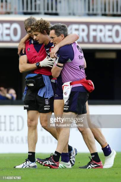 Nat Fyfe of the Dockers is assisted off the field after sustaining a head knock at Optus Stadium on April 07 2019 in Perth Australia