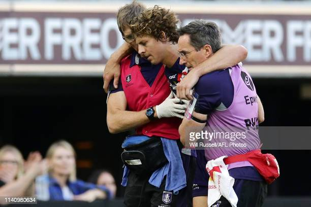 Nat Fyfe of the Dockers is assisted off the field after sustaining a head knock the 2019 AFL round 03 match between the Fremantle Dockers and the St...