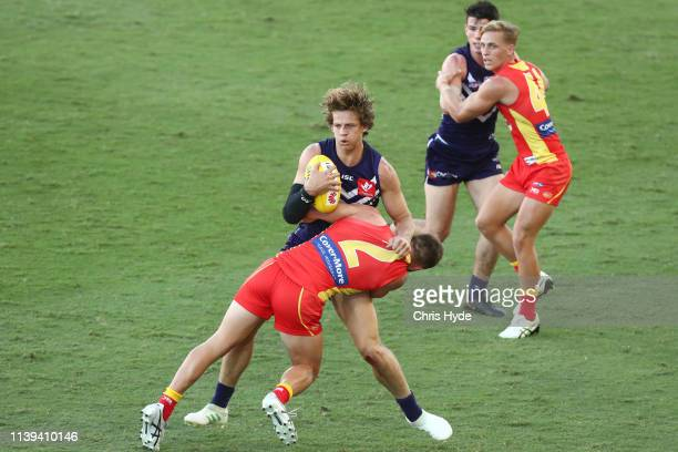 Nat Fyfe of the Dockers is tackled by Anthony Miles of the Suns during the round two AFL match between the Gold Coast Suns and the Fremantle Dockers...