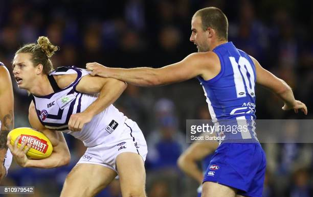 Nat Fyfe of the Dockers is tackled by Ben Cunnington of the Kangaroos during the round 16 AFL match between the North Melbourne Kangaroos and the...