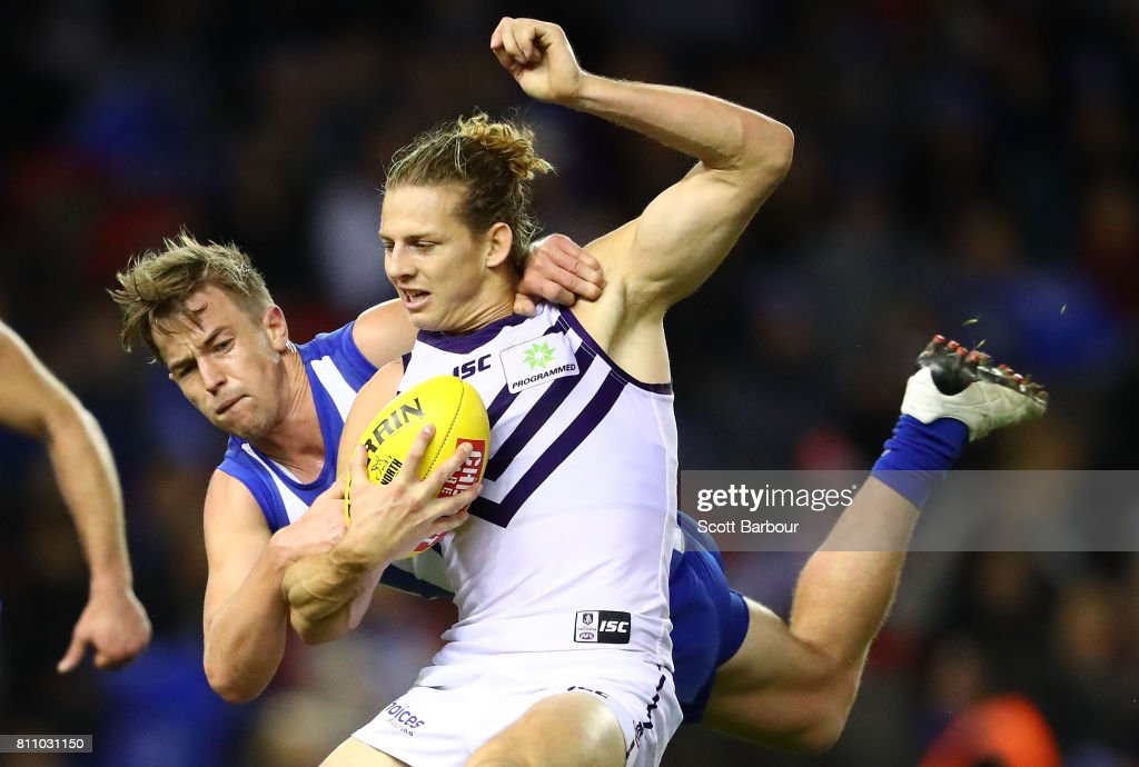 Nat Fyfe of the Dockers is tackled by Trent Dumont of the Kangaroos during the round 16 AFL match between the North Melbourne Kangaroos and the Fremantle Dockers at Etihad Stadium on July 9, 2017 in Melbourne, Australia.