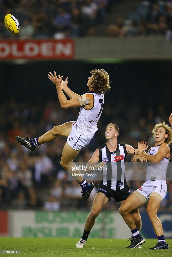 Nat Fyfe of the Dockers marks the ball ahead of Alan Toovey of the Magpies during the round one AFL match between the Collingwood Magpies and the Fremantle Dockers at Etihad Stadium on March 14, 2014 in Melbourne, Australia.