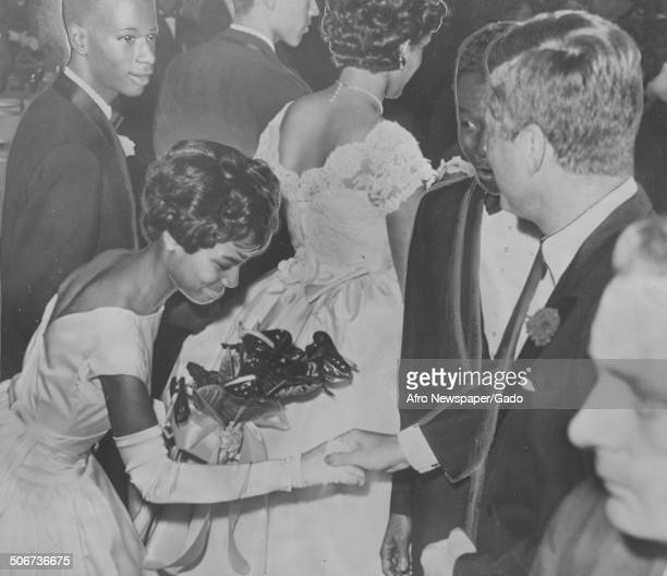 Nat King Cole and former United States President John F Kennedy greeting an AfricanAmerican debutante during a cotillion Beverly Hills California 1962