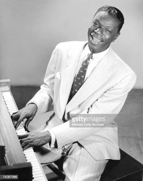 Nat 'King' Cole poses for a portrait with a piano on December 13 1951 in Los Angeles California