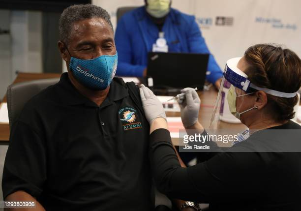 Nat Moore 69, former Miami Dolphin player, receives a Pfizer-BioNtech COVID-19 vaccine from Susana Flores Villamil, RN from Jackson Health System, at...