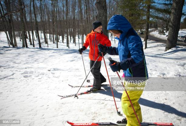 Nat Rathbone left and his friend Griffin Prescott both of Brunswick put their skis back on after crossing the road to another trail while nordic...