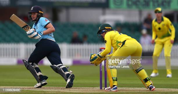 Nat Sciver of England hits the ball towards the boundary as Alyssa Healy of Australia looks on during the 1st Royal London Women's ODI between...