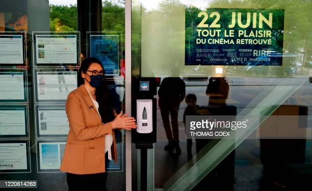 Natacha Bouchaudon director of the UGC movie Theatre cleans her hands at a dispenser of hydroalcoholic hand sanitizer gel placed outside a movie...