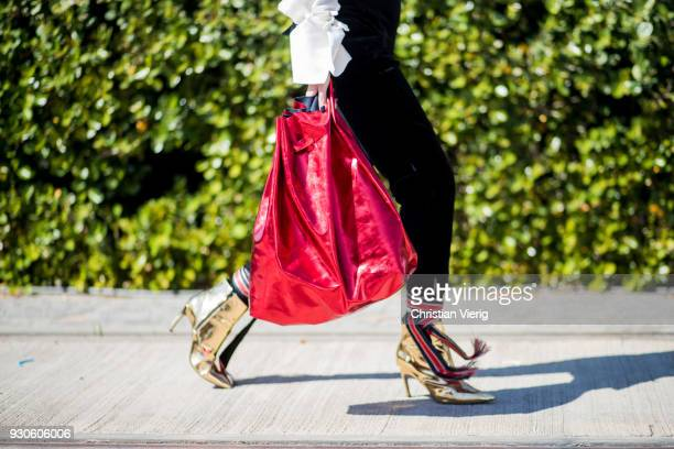 Nataf Hirshberg wearing golden boots red bag is seen during Tel Aviv Fashion Week on March 11 2018 in Tel Aviv Israel