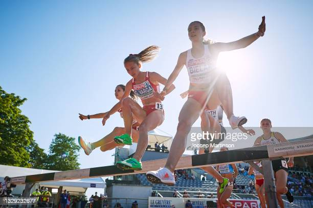 Natalia Bielak of Poland and Greta Varga of Hungary jump over a hurdle in the Women's 3000m Steeplechase Race during European Athletics U20...