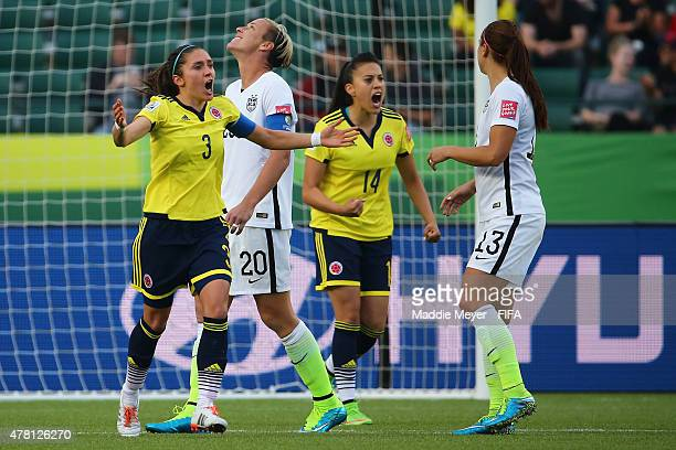 Natalia Gaitan of Colombia and Nataly Arias celebrate next to a dissapointed Abby Wambach of United States of America after missing a penalty kick...