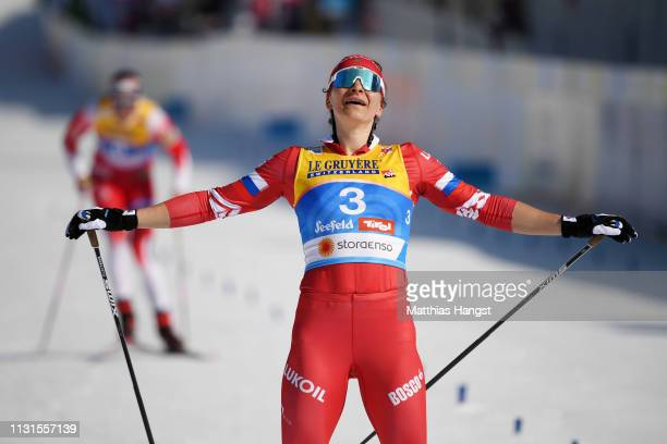 Natalia Nepryaeva of Russia celebrates as she crosses the finish line for third place in the Cross Country Skiathlon Ladies 15k race during FIS...