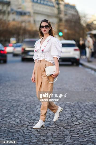 "Natalia Ostrofsky ""Mascarada Paris"" wears sunglasses, a hair brooch, a white shirt with red printed flowers, light brown pants, a white Miu Miu..."