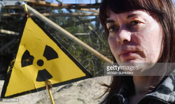 Natalia Shevchuk stands near a radioactive sign on April 23 2018 in the ghost town of Pripyat as she is revisiting her childhood home 32 years after...