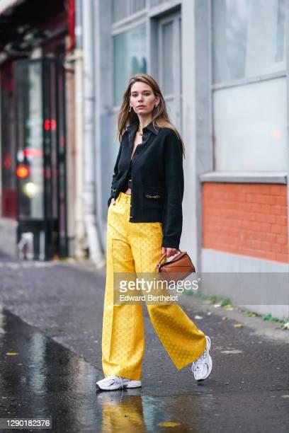 "Natalia Verza aka ""Mascarada Paris"" wears a black shirt, a black wool cardigan, a brown leather geometric Loewe bag, yellow monogram printed Gucci..."