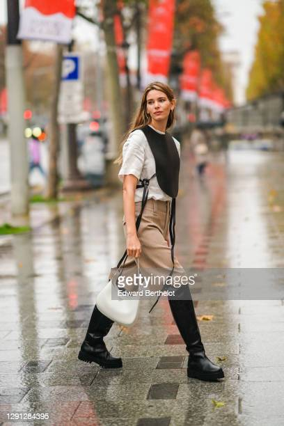 "Natalia Verza aka ""Mascarada Paris"" wears a white t-shirt, a black bib bustier from Loewe, beige cargo short pants from Chloe, black knee high..."