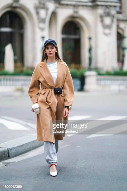 Natalia Verza aka Mascarada wears a black cap from Nike, a white t-shirt, a beige pale brown wool long trench coat, gray sport jogger pants, a golden...