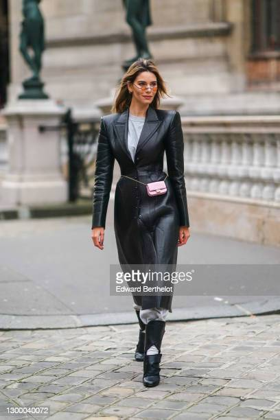 Natalia Verza aka Mascarada wears small circular sunglasses, a black leather long coat with shoulder pads from Fendi, a gray t-shirt, gray sport...