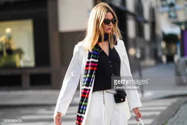 Natalia Verza aka Mascarada wears sunglasses, earrings, a long colored striped scarf, a black vest, a white oversized blazer jacket, a small Chanel...